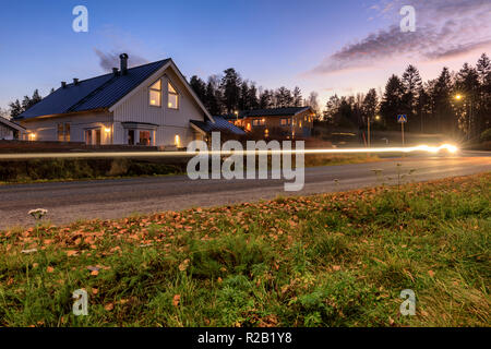 FLODA, SWEDEN - NOVEMBER 15 2018: Early evening long exposure of typical swedish detached house with light trails from passing car - Stock Photo