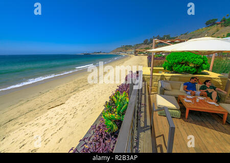 Malibu, California, United States - August 7, 2018: couple sitting at luxurious Japanese restaurant Nobu on famous Billionaire Beach or Carbon Beach for many famous people in Malibu. Summer holidays. - Stock Photo