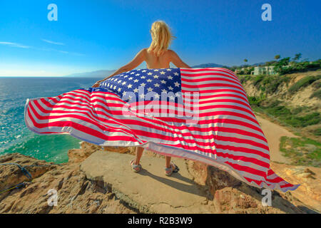 Freedom and patriotic concept. Woman holding an American flag waving from Point Dume promontory on Malibu coast in CA, United States. Caucasian female in California West Coast. - Stock Photo