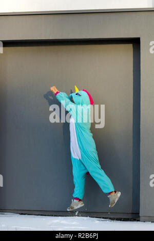 cute woman in kigurumi unicorn costume jump like superhero against gray wall on the street - Stock Photo