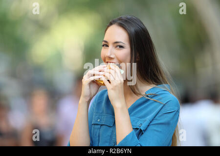 Happy woman biting a burger looking at camera in the street - Stock Photo