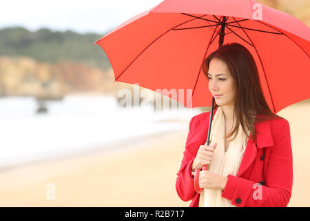 Serious woman in red contemplating the beach in winter under an umbrella - Stock Photo