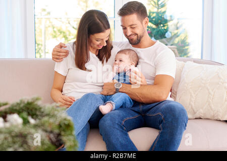Happy young family sitting on sofa with their baby girl and enjoy each other's company at Christmas time. - Stock Photo