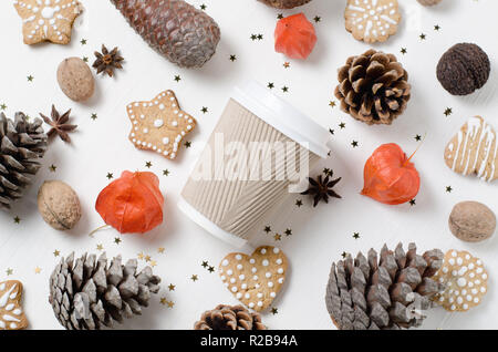 Takeaway paper coffee cup among cookies, pine cones and other christmas decor. Top view trendy background - Stock Photo