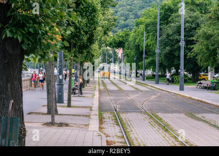 Budapest, Hungary, July 4: Danube Embankment with people walking and a tram in the background in the city of Budapest on July 4, 2018. - Stock Photo