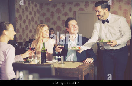 Polite adult waiter bringing ordered dishes to guests at restaurant - Stock Photo