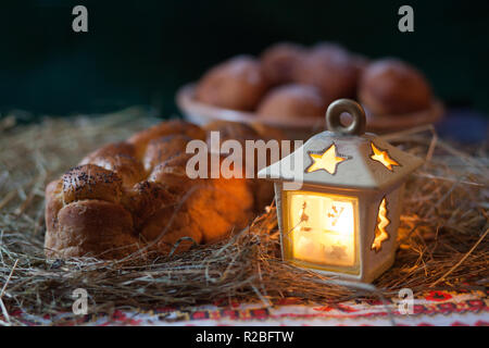 Christmas still life. Donuts and kalach on the table covered with hay. Traditional East Slavic bread. - Stock Photo