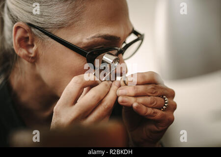 Mature female jeweler looking at stone through loupe to inspect it. Close up of senior jewelry maker looking at the gem while working at workshop. - Stock Photo