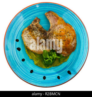 Top view of appetizing grilled pork loin with guacamole sauce and fresh leaves of arugula. Isolated over white background - Stock Photo