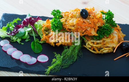 Deep-fried vegetables in batter served with mixed greens, slices of small radish and black olives - Stock Photo