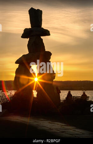 Vancouver Inukshuk Sunset. People out for a walk at sunset at English Bay, Vancouver. - Stock Photo