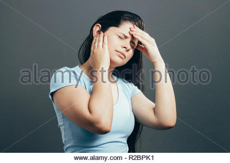 Young woman with ear pain, holding hand on his head on gray background - Stock Photo