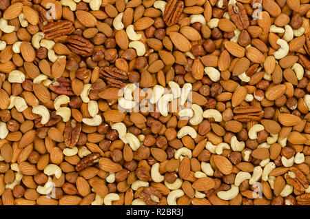 Mixed nuts, surface and background. Snack mix of dried almonds, cashews, hazelnuts and pecans. Trail mix, student food or fodder. - Stock Photo