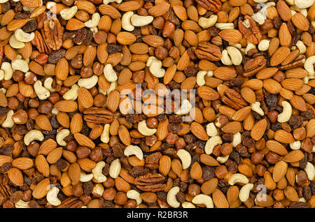 Nuts and raisins, surface and background. Snack mix of dried almonds, cashews, hazelnuts, pecans and raisins. Trail mix, student food or fodder. - Stock Photo