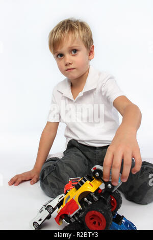 Small handsome boy playing with toys - Stock Photo