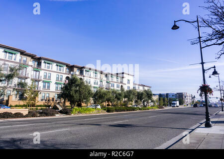 Light traffic on a street in Santa Clara on a sunny day, multifamily housing development on the side of the road; San Francisco bay area, California - Stock Photo
