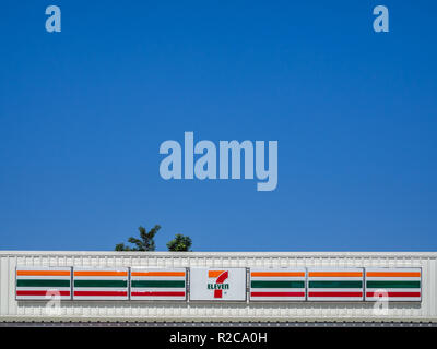 BANGKOK, THAILAND : November 1, 2017 : 7-Eleven sign on white store roof with tree on blue sky background on sunny day with copy space minimalist styl - Stock Photo