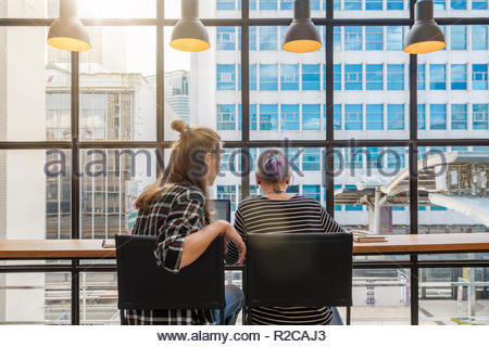 Backside of Hipster young couple freelancer using smart Laptop for working in the Loft cafe workplace. Creative Startup and entrepreneur business conc - Stock Photo