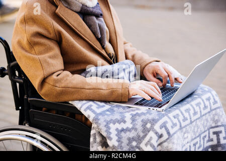 cropped shot of disabled man in wheelchair using laptop on street - Stock Photo