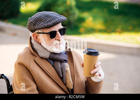 close-up portrait of senior disabled man in wheelchair holding paper cup of coffee on street - Stock Photo
