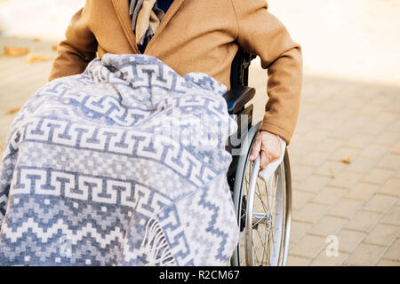 senior disabled man in wheelchair with plaid on legs riding by street - Stock Photo