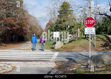 Couple walking on Shining Sea Bikeway  in Falmouth, Cape Cod at road crossing with Cyclists Dismount to Cross Street, No Motor Vehicles & Stop signs - Stock Photo
