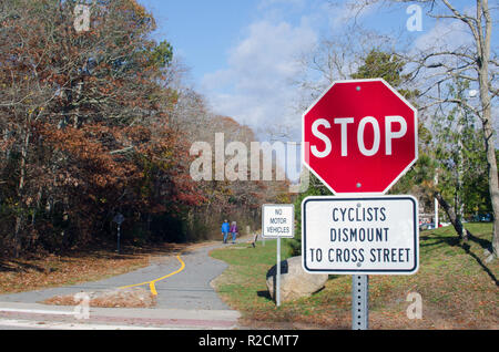 Shining Sea Bikeway sign with Stop sign, No Motor Vehicles sign and Cyclists Dismount to Cross Street in Falmouth, Cape Cod, Massachusetts USA - Stock Photo