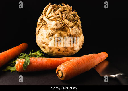 Vegetables and knife - black background. Carrots, celery root, arugula - Stock Photo