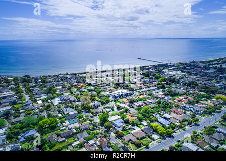 Aerial view of residential area near ocean coastline and long wooden pier with sailboats. - Stock Photo