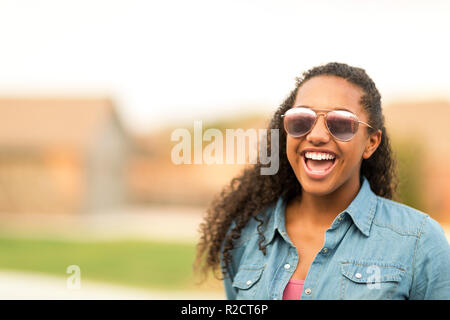 Portriat of a young teenage girl laughing. - Stock Photo