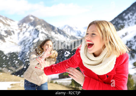 Two funny friends joking throwing snowballs in the mountain on winter holiday - Stock Photo
