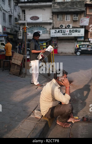 A man in the business area of Bhuleshwar in Mumbai, India, speaking on his mobile phone, adopting a 'rural-type' squatting position - Stock Photo