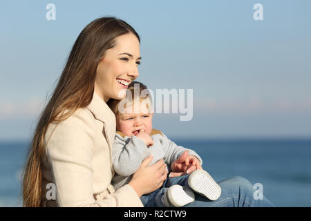 Happy mother and her son looking forward on the beach - Stock Photo