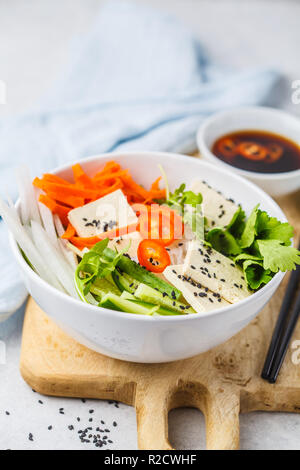 Vietnamese rice noodle with tofu and chilli vegetables salad in white bowl, top view. - Stock Photo