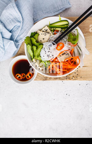 Vietnamese rice noodle with tofu and chilli vegetables salad in white bowl, top view, copy space. - Stock Photo