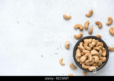 Cashew nuts in bowl on grey concrete background with copy space for text. Top view, healthy vegetarian food - Stock Photo