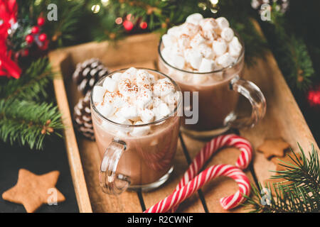 Hot chocolate with marshmallows, warm cozy Christmas drink in a wooden tray - Stock Photo