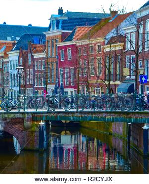 Colorful canal houses in Amsterdam in Netherlands, many bicycles on a bridge over a canal, April - Stock Photo