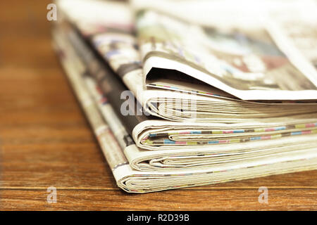 Pile of fresh morning newspapers on wooden table at the office. Business news  in daily papers. Folded and stacked yellow pages with selective focus. - Stock Photo