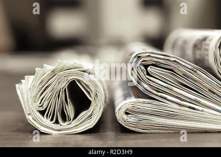 Morning newspapers and journals on table at office. Latest financial and business news in daily papers. Pages with headlines, articles, photos, text - Stock Photo