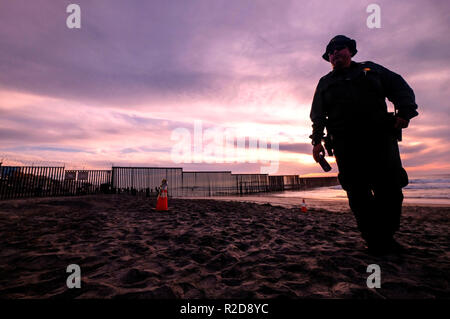 Los Angeles, USA. 17th Nov, 2018. A U.S. Border Patrol agent stands in front of the border fence that divides the U.S. and Mexico in San Diego, California, the United States, Nov. 17, 2018. Officers of the U.S. Customs and Border Protection (CBP) have tightened preparations at the U.S.-Mexico border in San Diego, California, for the arrival of massive caravans of Central American migrants. Credit: Zhao Hanrong/Xinhua/Alamy Live News - Stock Photo
