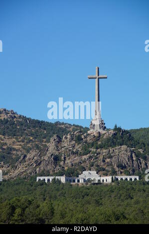 04 October 2018, Spain, El Escorial: A 155 meter high and 44 meter wide concrete cross stands on the mountain peak Risco de la Nava in the Valle de los Caídos (Valley of the Fallen) about 60 kilometers northwest of Madrid. In the monument in the Sierra de Guadarrama is the tomb of the Spanish dictator Franco. Three days after his death, he was buried in the Basilica on 23 November 1975. The mausoleum, which was driven into the rock by 20,000 forced laborers between 1940 and 1959, is considered one of the largest in the world. It is the most important architectural symbol of Franco's dictators - Stock Photo