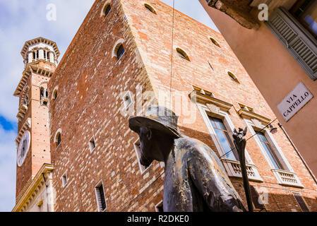 The poet, sculpture of Berto Barbarani, looks at the Lamberti Tower. Piazza delle Erbe. Verona, Veneto, Italy, Europe - Stock Photo