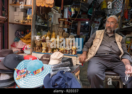 An Arabic storekeeper in the Old City sitting and holding and manipulating worry beads. In Jerusalem, Israel. - Stock Photo