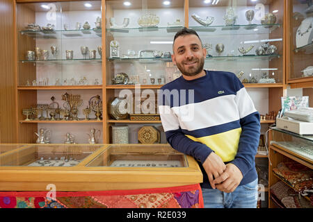 Posed portrait of an Arabic storekeeper in an upscale gift shop in the Old City, Jerusalem, Israeli. - Stock Photo