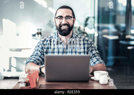 Cheerful bearded man wearing glasses smiling after successful day - Stock Photo