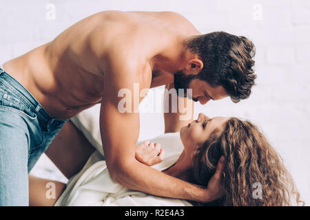 side view of shirtless handsome man laying on beautiful curly girlfriend in bedroom at home - Stock Photo