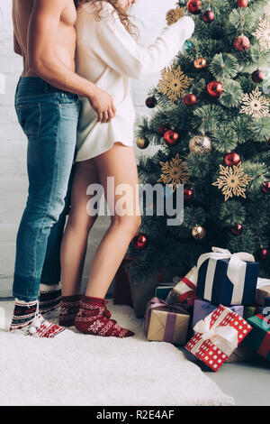 cropped image of shirtless muscular man embracing girlfriend near decorated christmas tree at home - Stock Photo