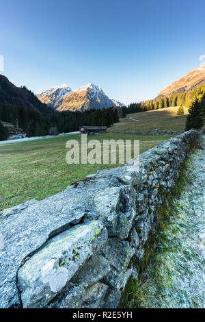 mountain landscape and valley with forest and snow-capped mountain peaks and an old rock wall with wooden huts and chalets behind - Stock Photo