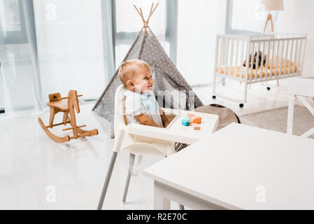 happy toddler sitting in baby chair in nursery room with toy cubes
